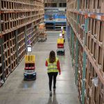 Woman walking down warehouse aisle with robots