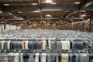 Warehouse with garments on hanger in foreground and cased inventory in background